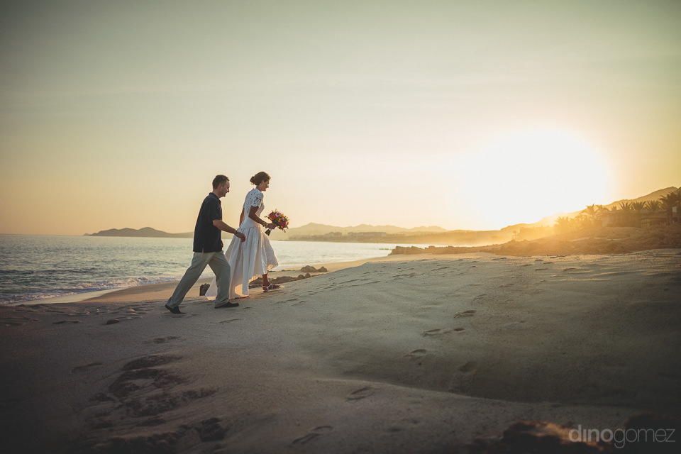 bride and groom walk off into the sunset in los cabos