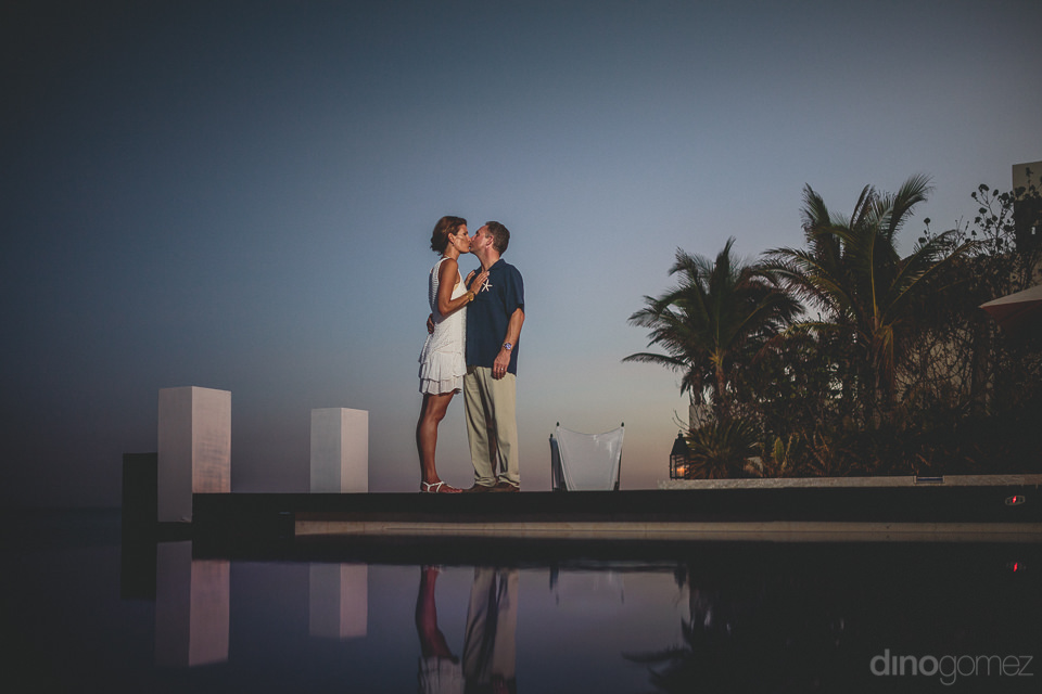 newlyweds kiss next to infinity pool at cabo resort