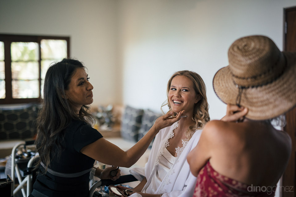 bride smiles while she has her wedding makeup done by olga busto