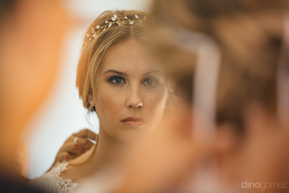 bride looks at herself confidently in the mirror before the wedd