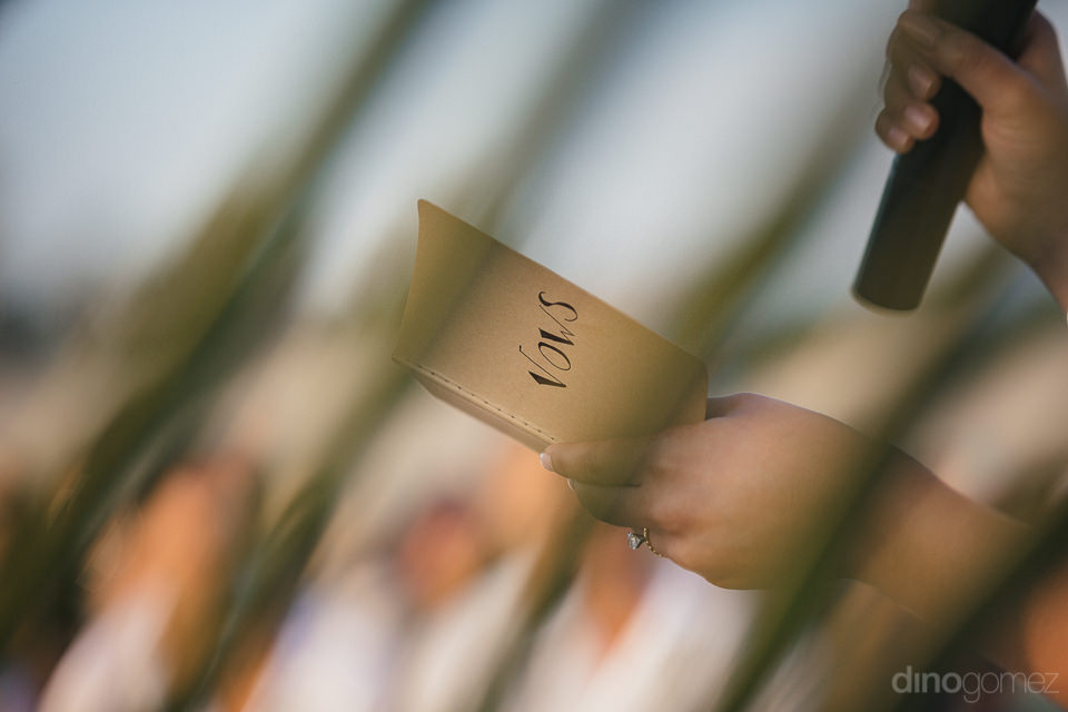 bride holds wedding vows paper and reads them into microphone du