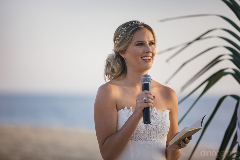 bride holds microphone speaks vows while standing at a wedding a