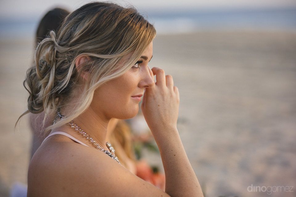 bridesmaid cries during wedding ceremony on the beach