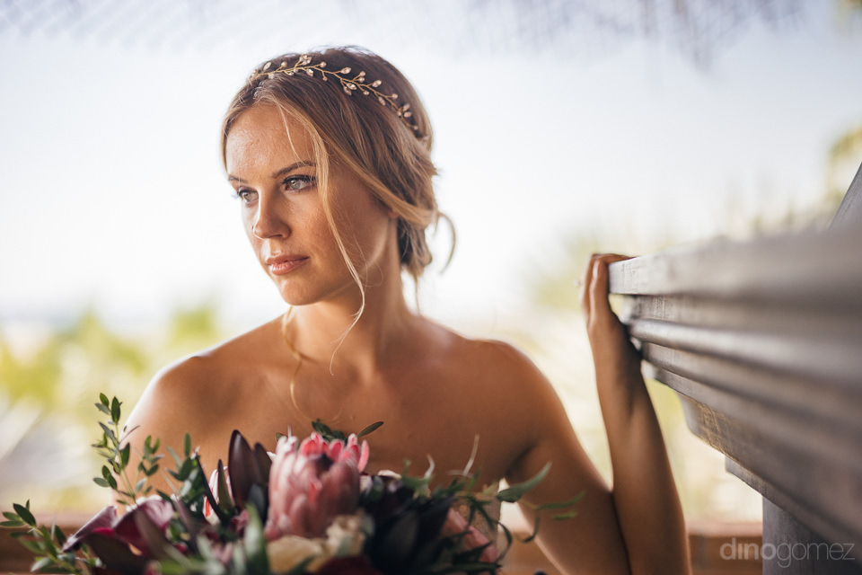 bride on sunny hotel balcony on her wedding day in todos santos
