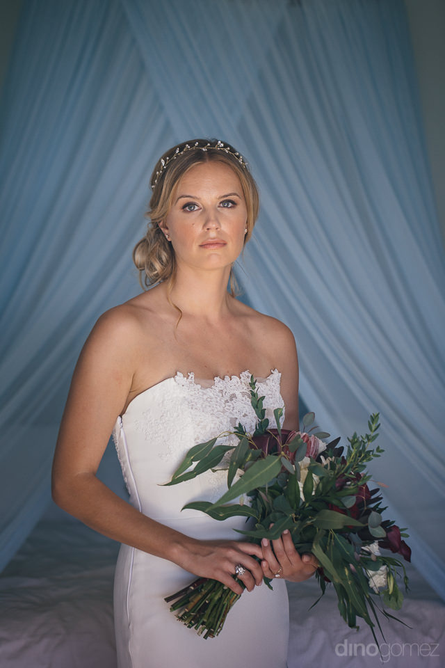 blonde bride holding unique green and purple bouquet against coo