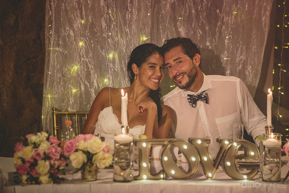 young newlyweds sit together at glamorous head table during wedd