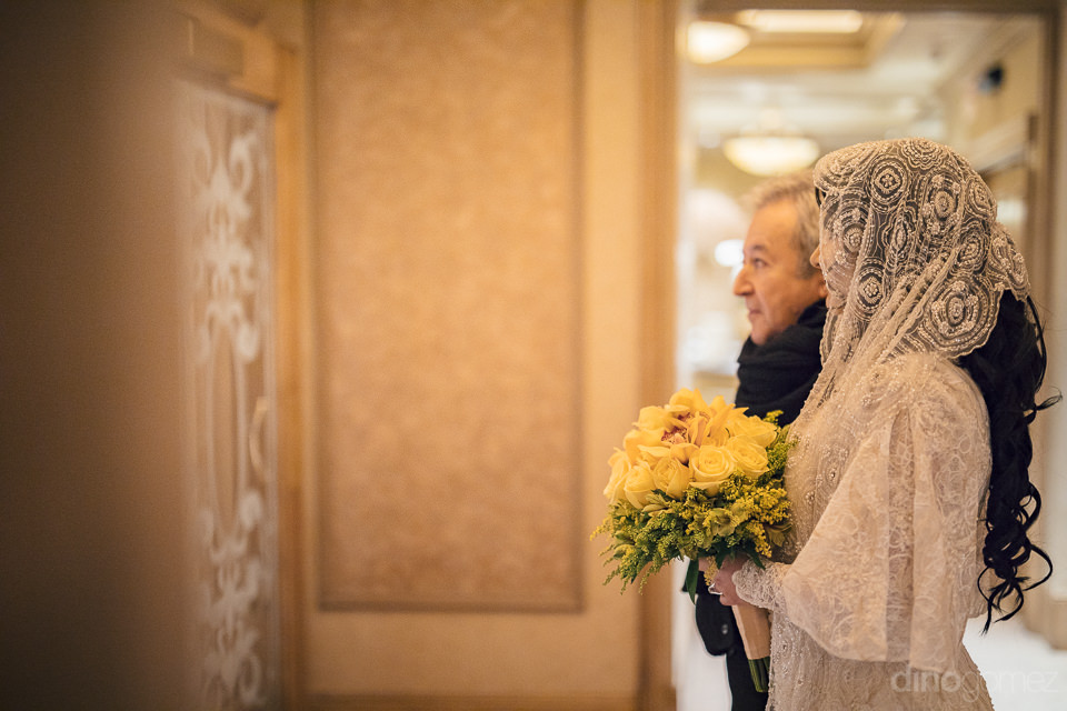 bride holds yellow rose bouquet and waits outside wedding hall o