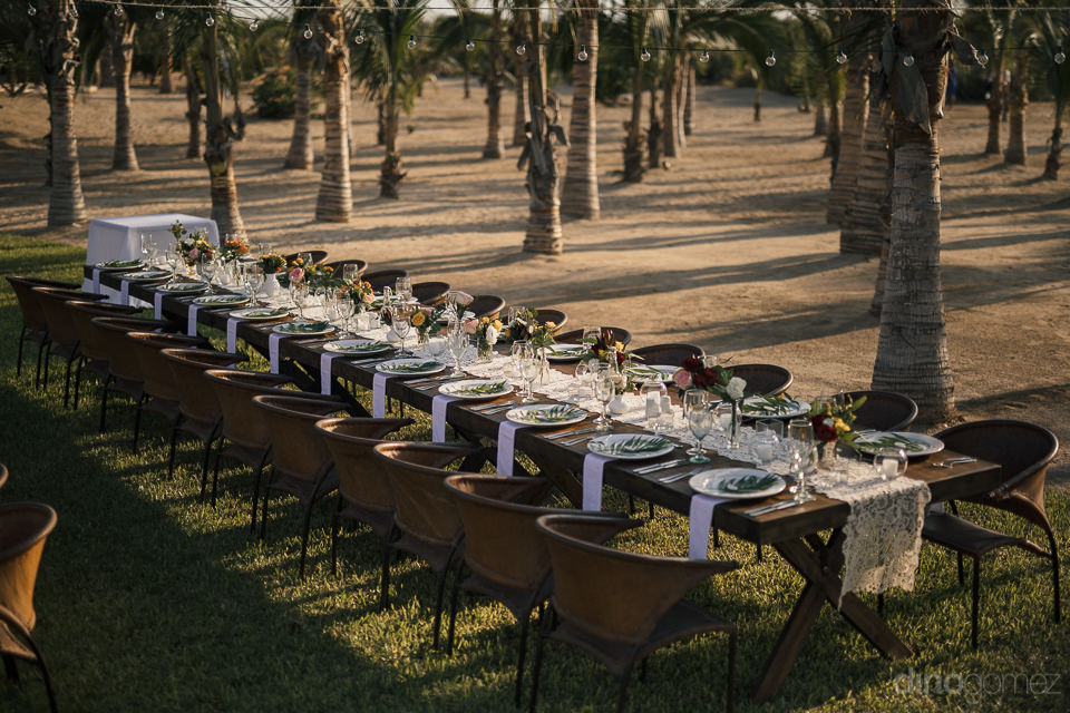 long picnic style wedding dinner table at outdoor beach wedding