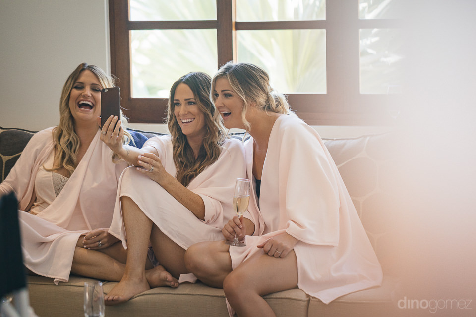 three bridesmaids in pink bath robes take a selfie together on t