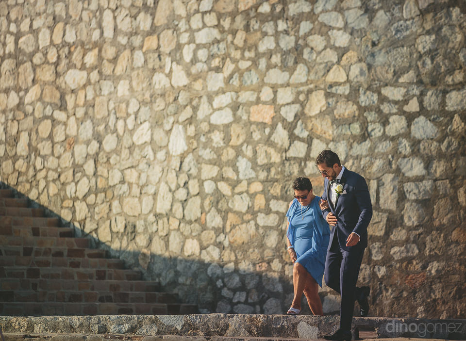 groom walks with mother in front of huge stone wall on wedding d