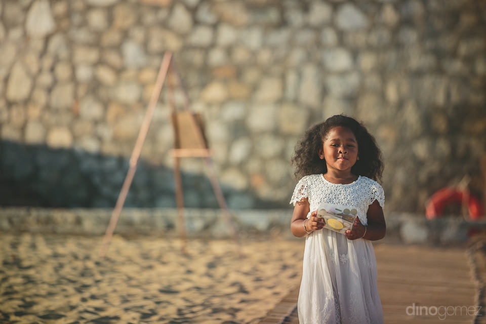 cute flower girl walks towards beach altar at cabo san lucas des