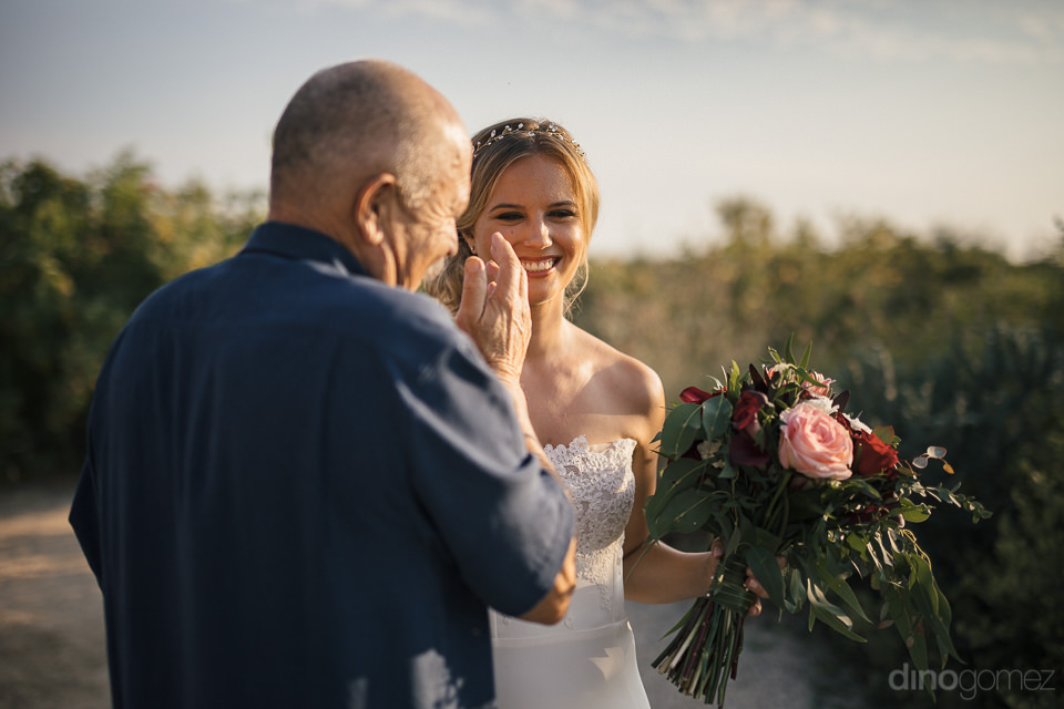 bride and her father laugh together on the beach before the star