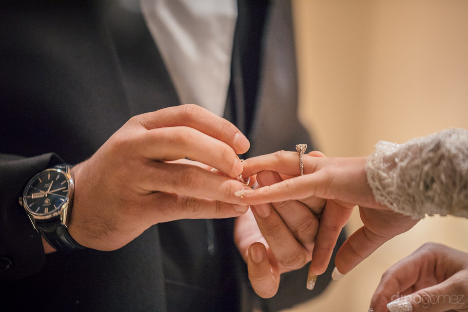 closeup photo of the groom putting the wedding band onto the bri