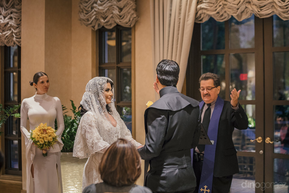 newlyweds standing at altar when priest pronounces them as husba