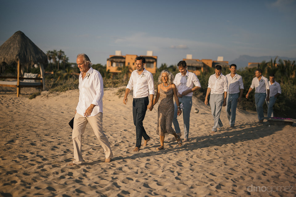 wedding guests walk barefoot through the sand towards the beach