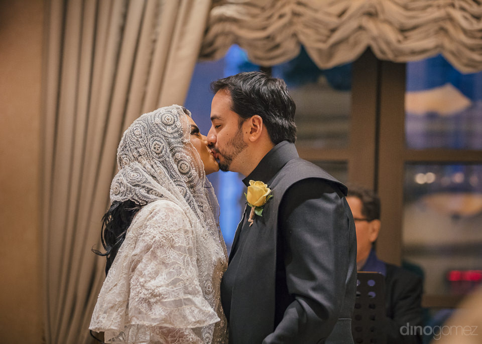newlyweds kiss for first time as husband and wife standing at we