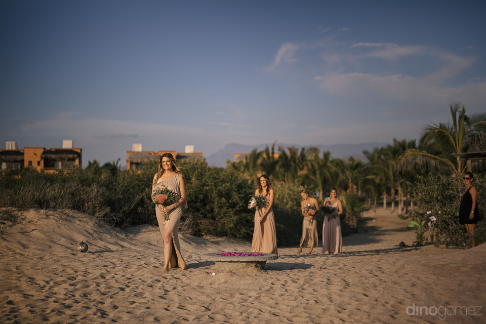 storybook wedding bridesmaids walking single file in the sand to