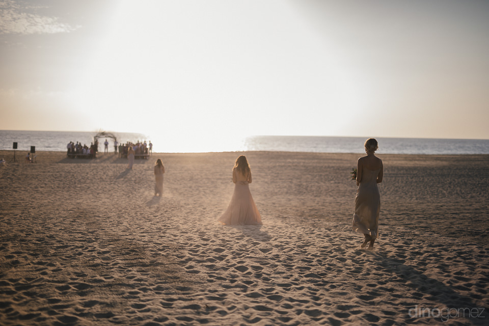 bridesmaids walk in sand on big beach to the wedding ceremony do