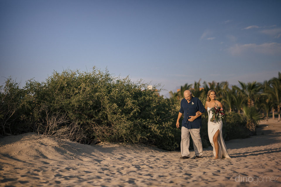 bride and father walking through sand on beach are last to arriv