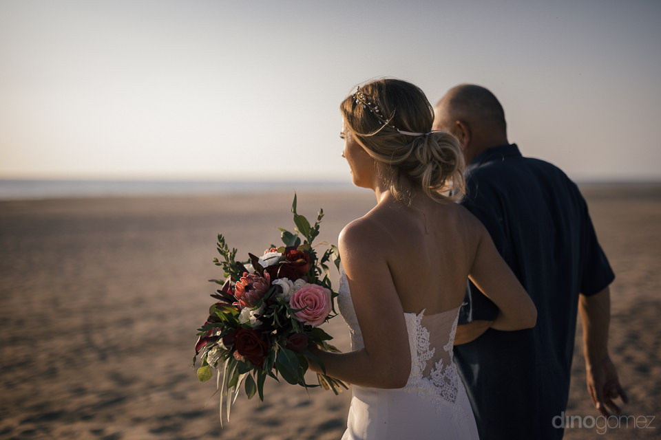 bride holding bouquet is accompanied by her dad while she walks