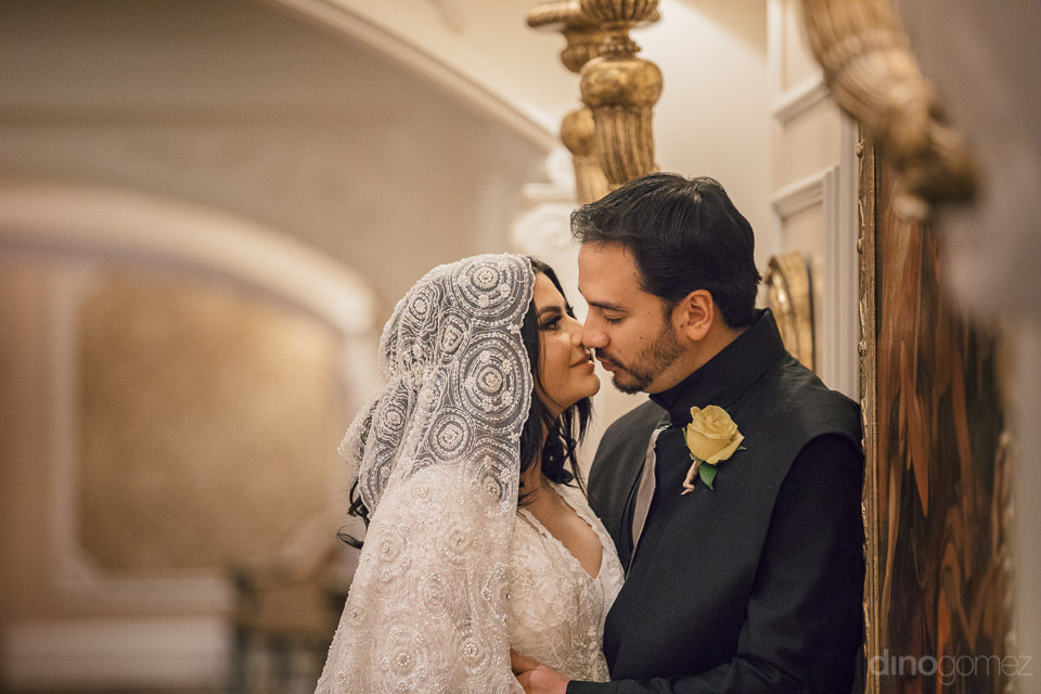 bride and groom kiss during photo session with renowned wedding