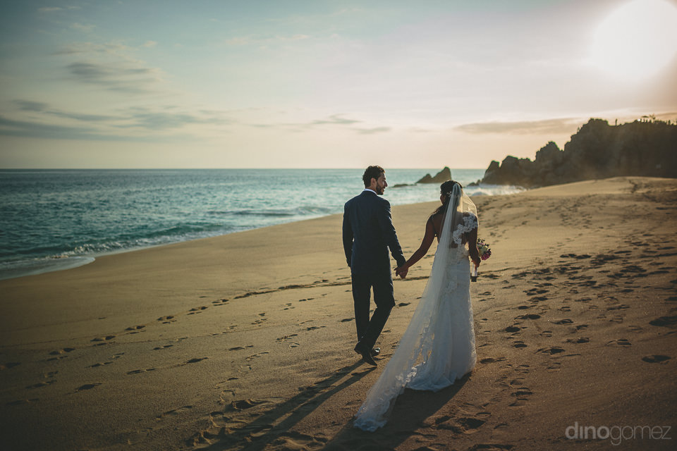 dream wedding at pueblo bonito newlyweds walk on beach into the