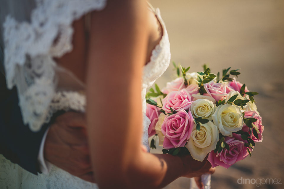 amazing white and pink rose bouquet in hands of bride as she wal