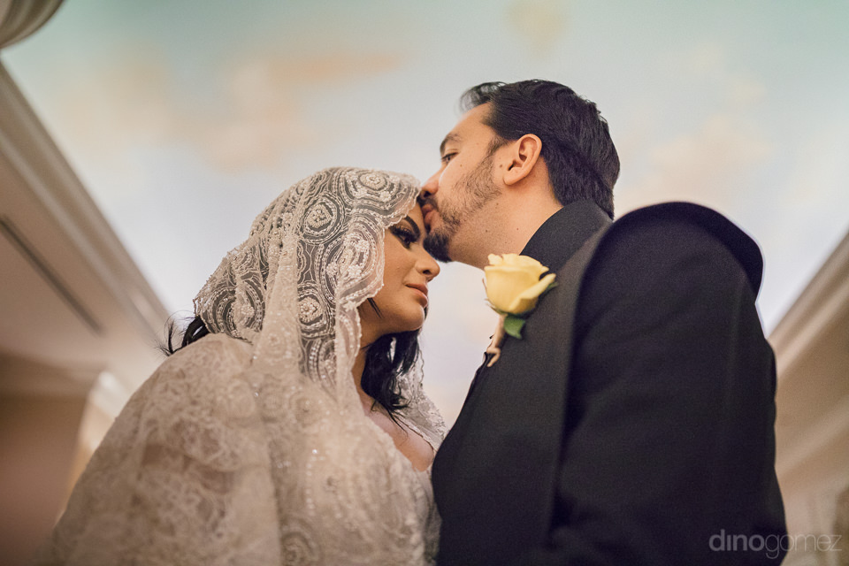 groom kisses bride on forehead with sky ceiling in background in
