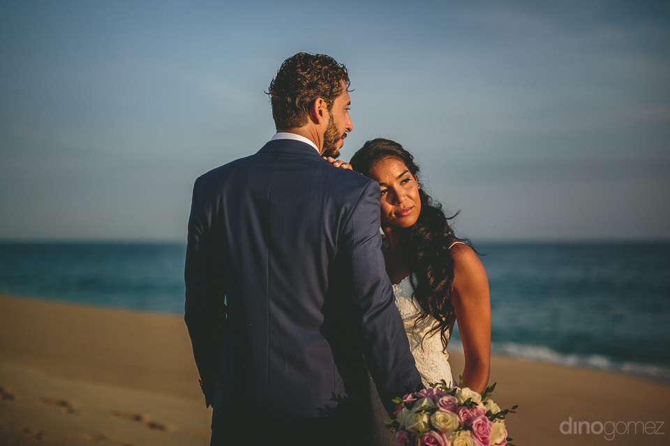dapper young newlyweds stand together on cabo san lucas beach in