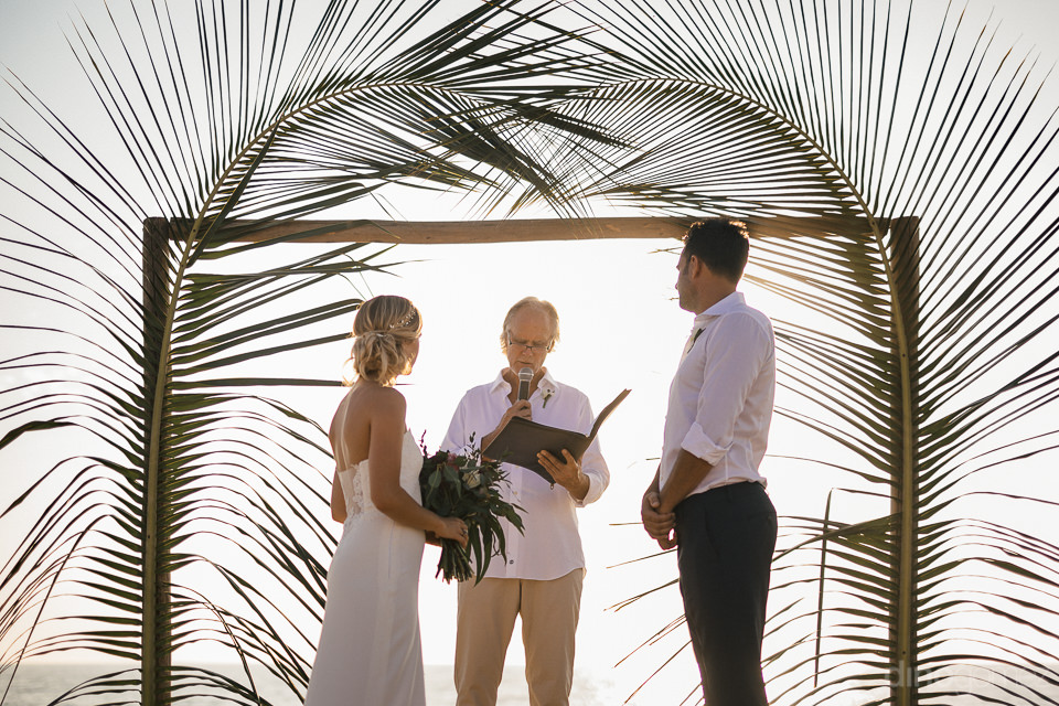 bride and groom and wedding priest at palm leaf altar during wed