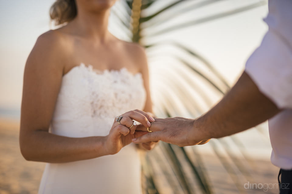 bride puts wedding ring on grooms finger at their wedding ceremo