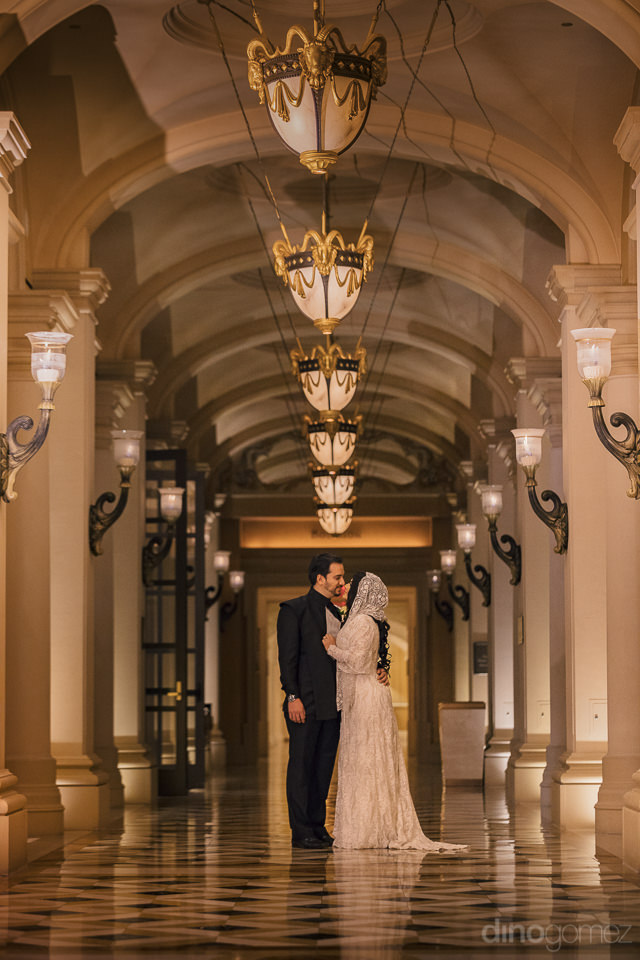 newlyweds together in lavish hotel palace hallway