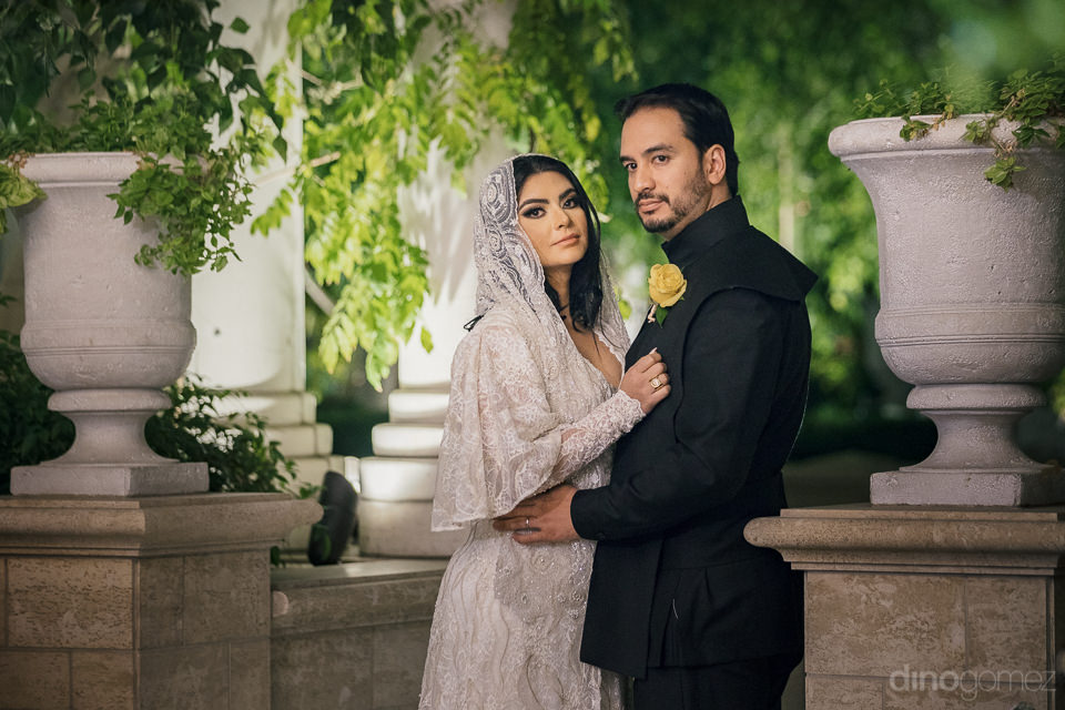 newlyweds stand in lush green garden in wedding photo by las veg