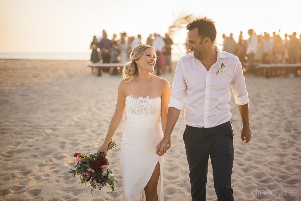 newlyweds walk away from wedding ceremony hand in hand on the be