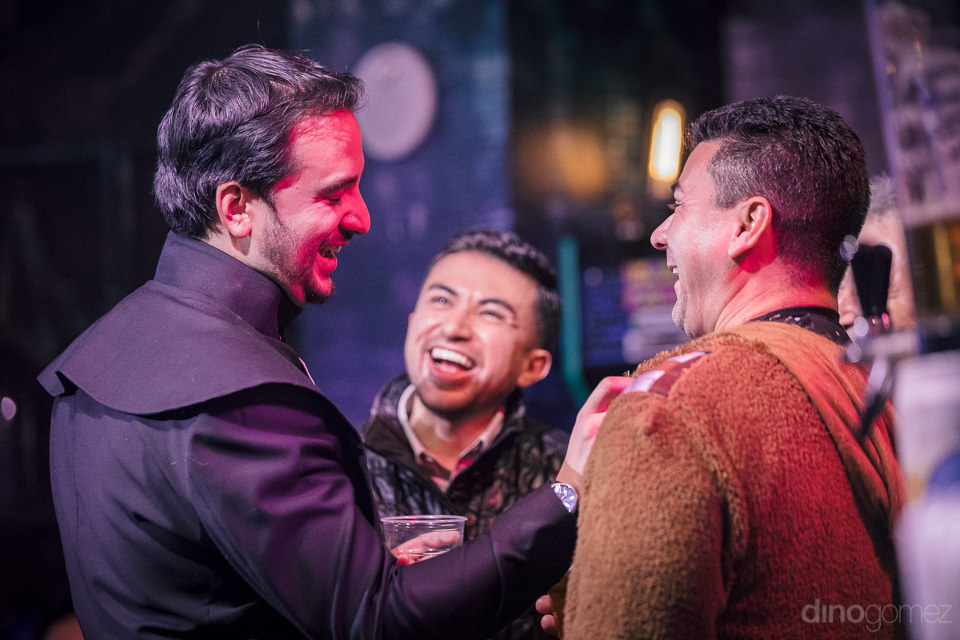 groom and friends dressed as star wars jedi knights laugh togeth