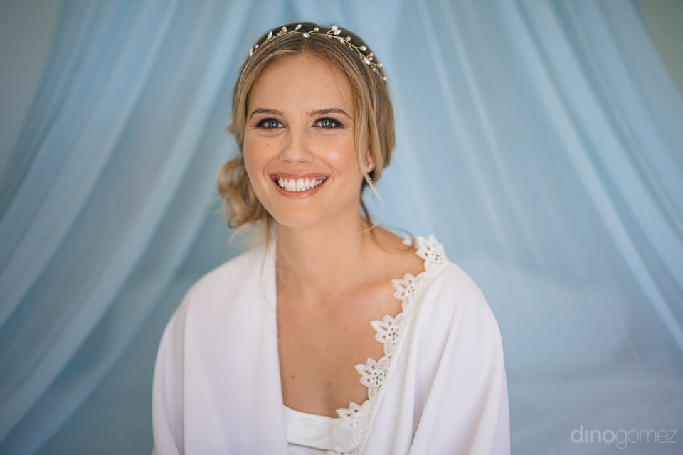 portrait photo of blonde bride before wedding against blue backg