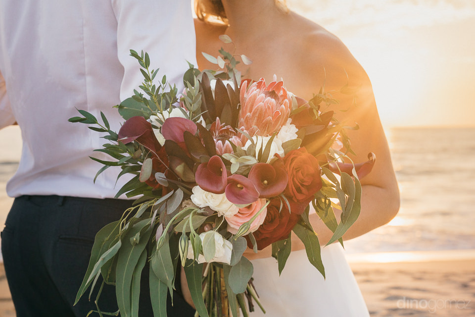 closeup photo of brides bouquet with dark red flowers and green