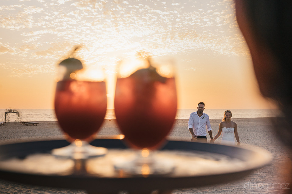 waiter delivers two glasses of red mexican sangria to the newlyw