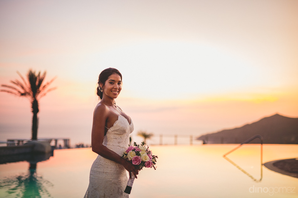 gorgeous sunset colors reflected in pool and sky with bride in w
