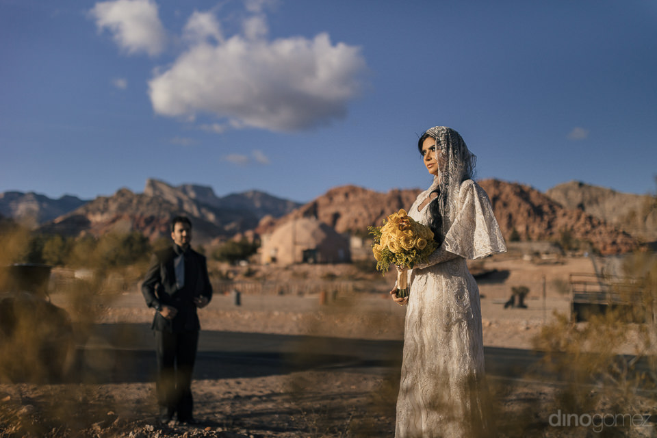 groom looks at bride from a distance in desert photo reminiscent