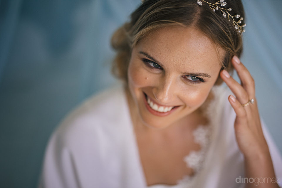 glimmering bride wearing floral diamond tiara and ring smiling a