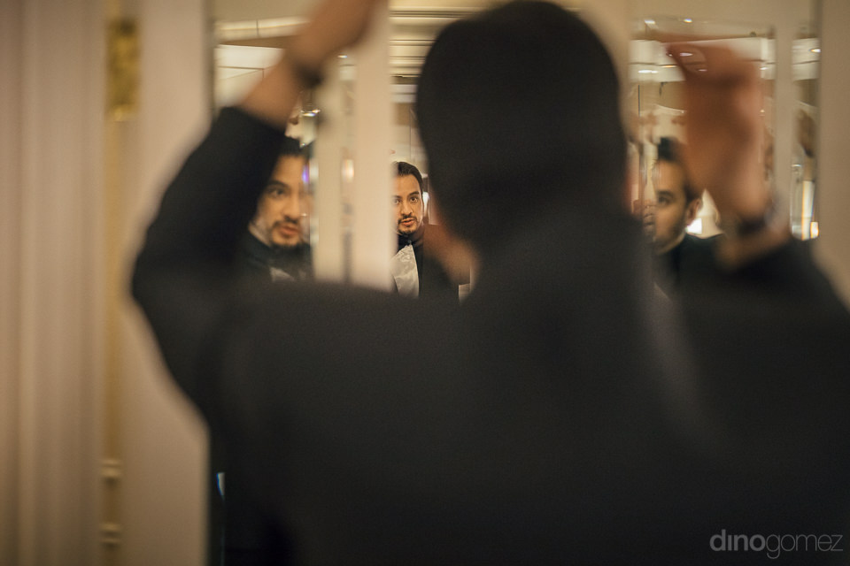 groom reflected by many mirrors in bathroom of venetian as he pr