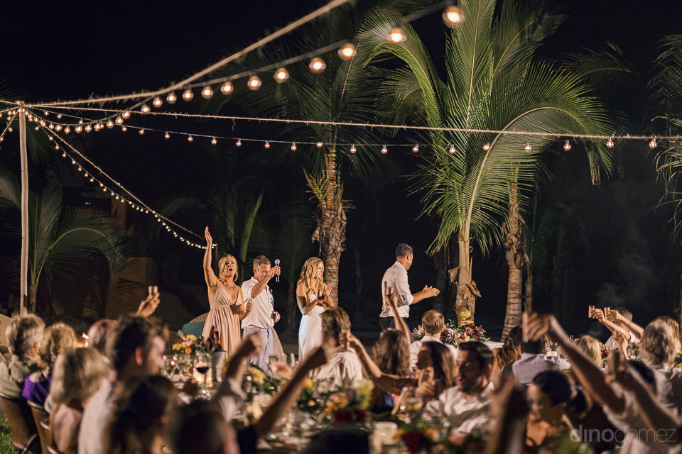 wedding guests raise glasses and toast bride and groom after spe