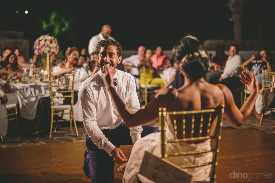 groom laughs smiles as bride invites him to remove her wedding b