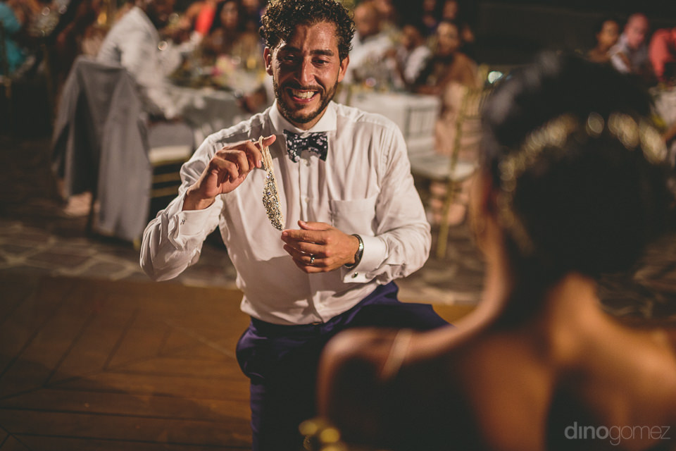 wedding guests laugh as groom holds up brides garter