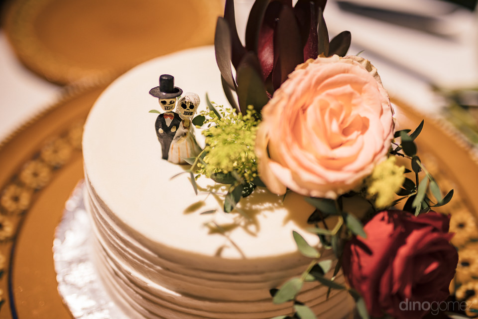 simplistic white wedding cake with flowers and mexico day of the
