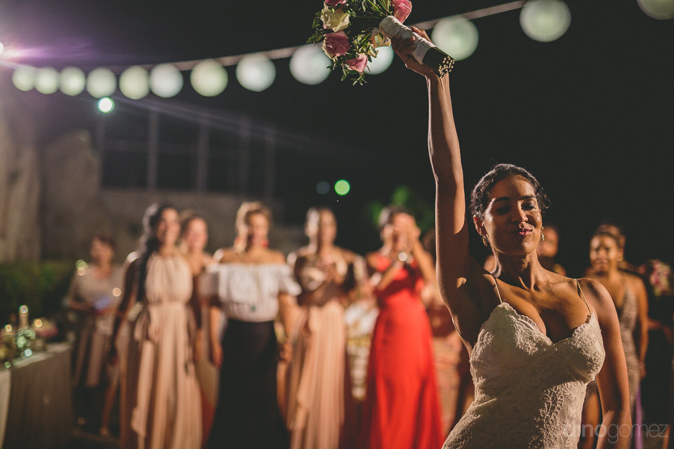 bride holds up bouquet just before throwing it to ladies gathere