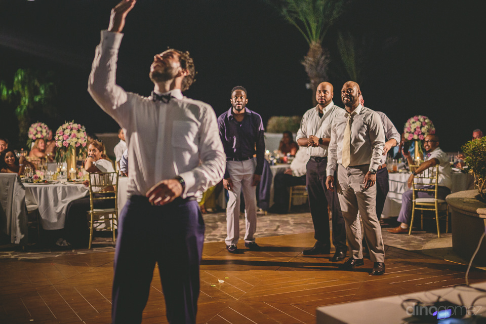 men gather on dance floor as groom throws brides garter over his