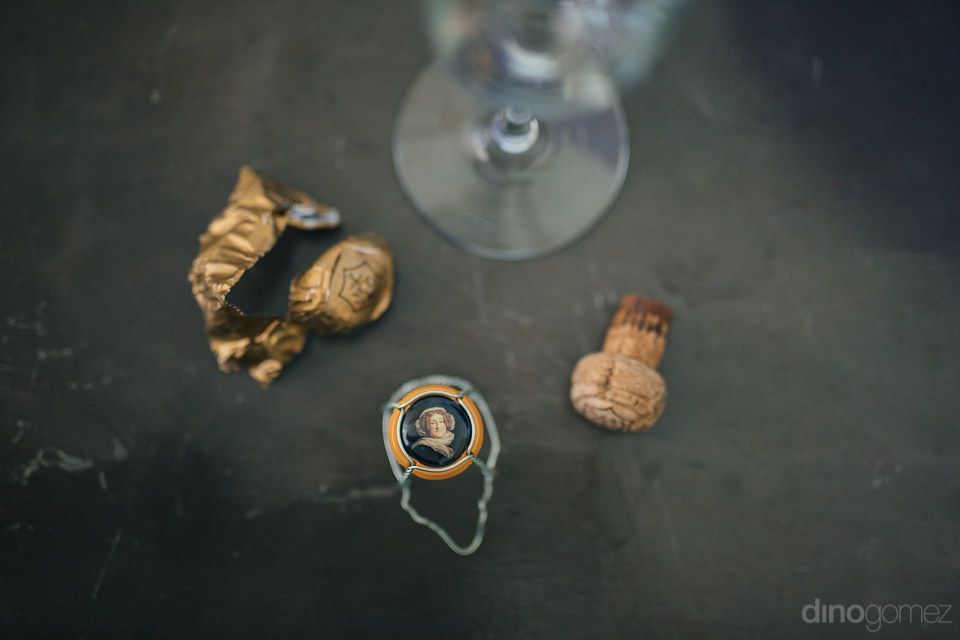 champagne cork cage wrapper and glass lie on table during todos