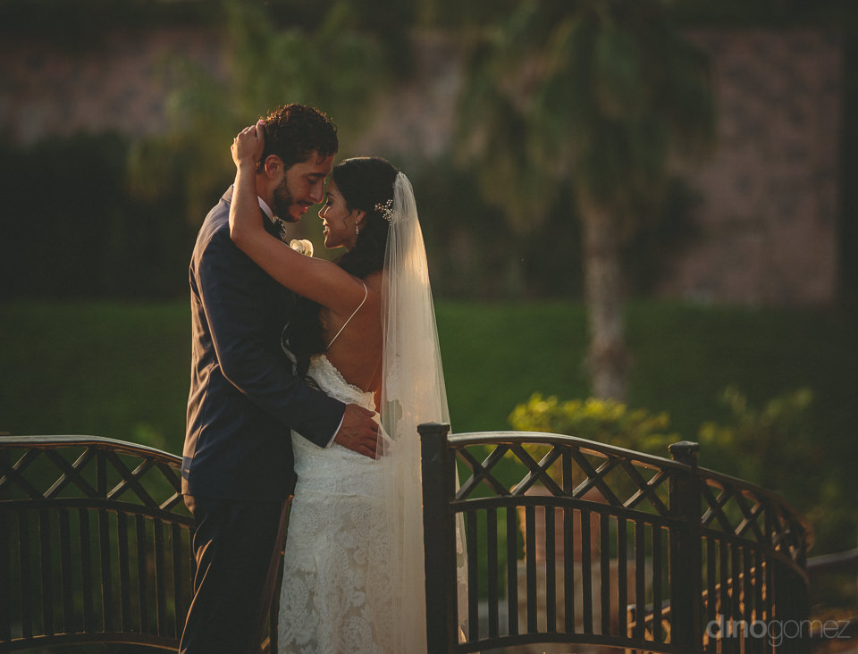 newlywed husband and wife embrace in the garden of a luxury reso